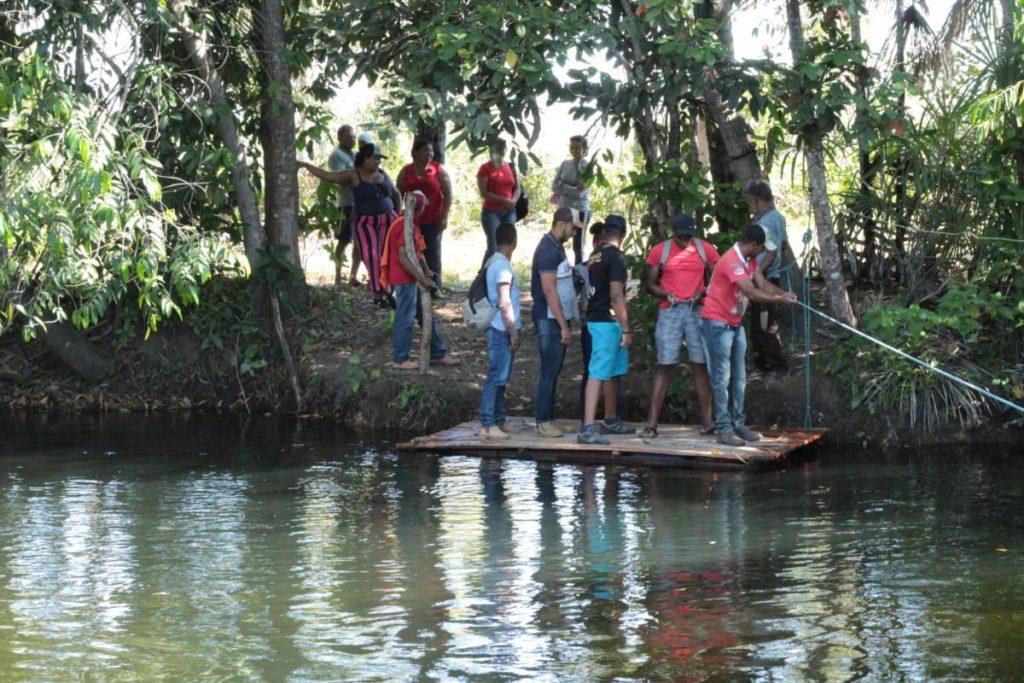 Quilombolas precisam atravessar rio para chegar à roça, onde cultivam mandioca, arroz e outros alimentos